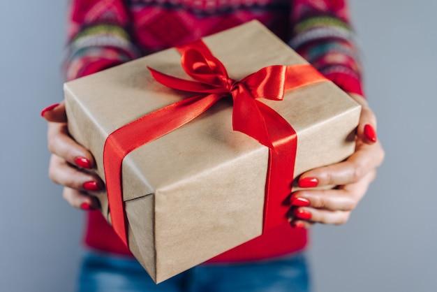 Beschnittener schuss des mädchens im gestrickten pullover mit traditionellem weihnachtsmuster, das geschenkbox hält, eingewickelt in bastelpapier und verziert mit rotem satinband Premium Fotos