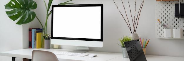 Beschnittener schuss des minimalen schreibtischs mit computer des leeren bildschirms, büromaterial und dekorationen