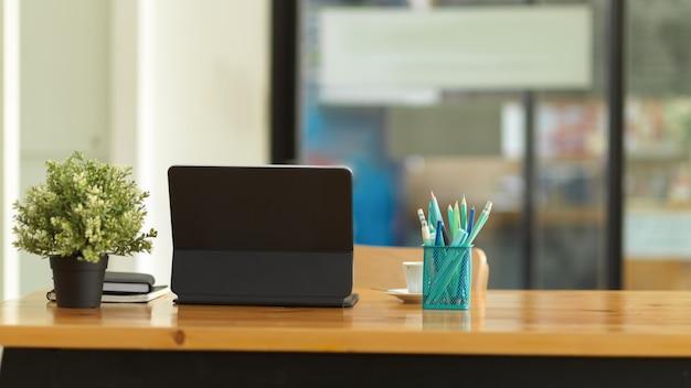 Beschnittener schuss des schreibtischs mit digitalem tablett, briefpapier, blumentopf und kopierraum im büroraum