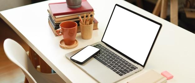Beschnittener schuss des studientischs mit laptop-smartphone-buchbriefpapier und -becher im wohnzimmer-beschneidungsweg