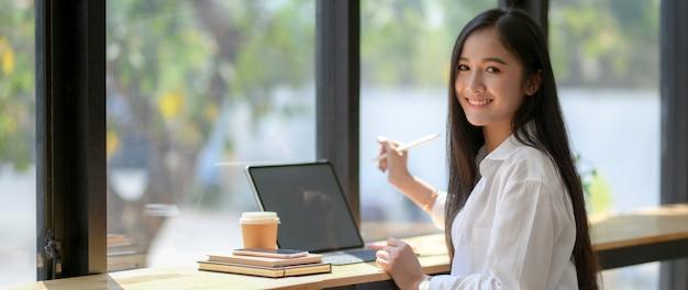 Beschnittener schuss des universitätsstudenten, der am kaffeehaus beim arbeiten mit tablette sitzt