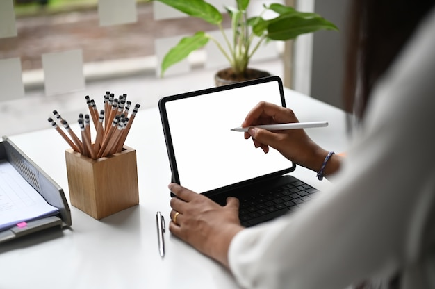 Beschnittener schuss einer frau, die digitales tablett verwendet und auf weißen bildschirm zeigt