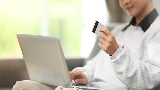 Beschnittener schuss einer jungen frau, die kreditkarte hält und computertablett auf sofa zu hause verwendet