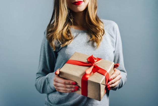 Beschnittener schuss eines mädchens mit roten lippen und polierten nägeln, die geschenkbox halten, eingewickelt in bastelpapier und verziert mit rotem satinband