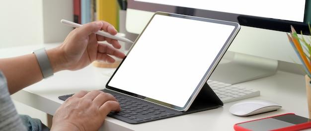 Beschnittener schuss eines mannes, der auf digitalem tablett im minimalen schreibtisch arbeitet