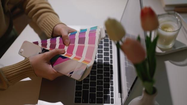Beschnittener schuss von designerhänden, die farbmuster halten, während mit laptop im heimbüro arbeiten