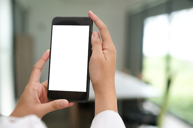 Beschnittener schuss von händen, die verspottetes smartphone mit leerem bildschirm im büro halten.