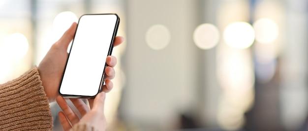 Beschnittener schuss von weiblichen händen, die smartphone halten, schließen beschneidungspfadbildschirm im unscharfen hintergrund des bokeh ein