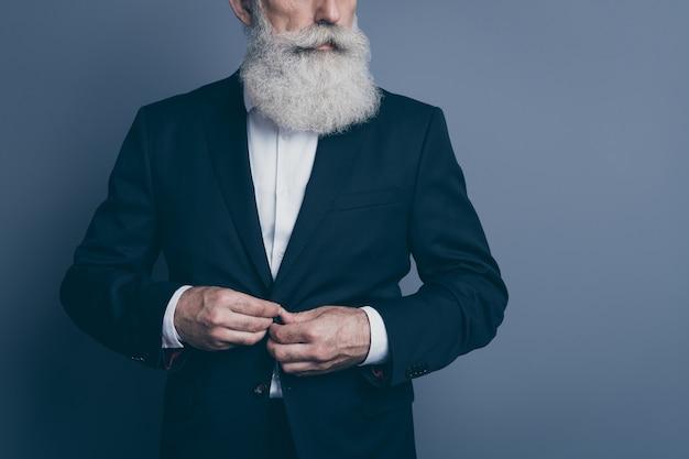 Beschnittenes ansichtsporträt seines er schönen attraktiven modischen modischen ernsthaften inhalts grauhaariger mann macho, der smokingverschlussknopf bereitstellt, der lokalisiert über dunkelgrauem pastellfarbhintergrund vorbereitet