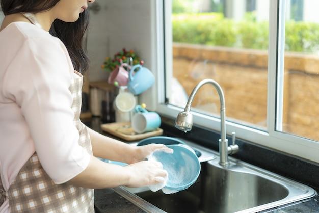 Beschnittenes bild der asiatischen attraktiven jungen frau spült geschirr in der spüle in der küche