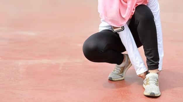 Beschnittenes bild der asiatischen muslimischen frau in der schwarzen sportbekleidung, die draußen mit schlanken athletischen beinen joggt. sportliche mädchenhände machen pause und binden schuh. nach dem workout. outdoor-konzept für gesundheit und lebensstil