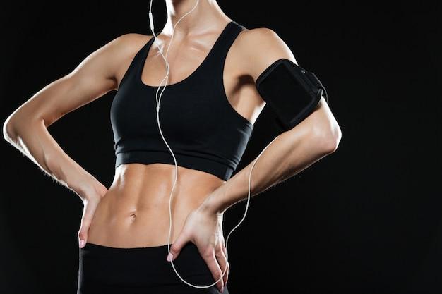 Beschnittenes bild der fitnessfrau, die arme auf hüften hält