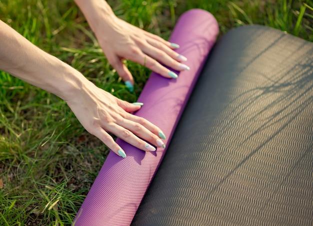 Beschnittenes bild der frau, die yogamatte auf gras setzt