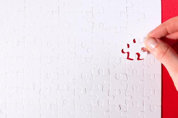 Beschnittenes bild der geschäftsfrau, die das letzte fehlende puzzle auf rot einfügt