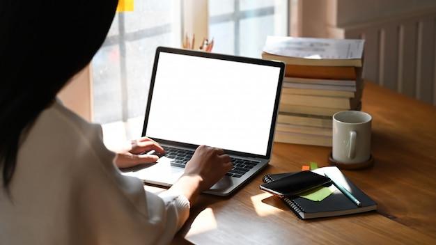 Beschnittenes bild der hände der sekretärin, die auf computer-laptop mit weißem leerem bildschirm tippt, der auf geordneten arbeitstisch setzt, der mit notizen, kaffeetasse und stapel bücher umgeben ist.