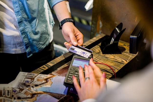 Beschnittenes bild der hände des jungen mannes, der für hotelzimmer an der rezeption unter verwendung einer kreditkarte bezahlt