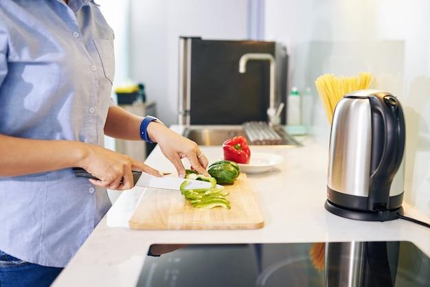 Beschnittenes bild der hausfrau, die am küchentisch steht und paprika für gesunden salat schneidet