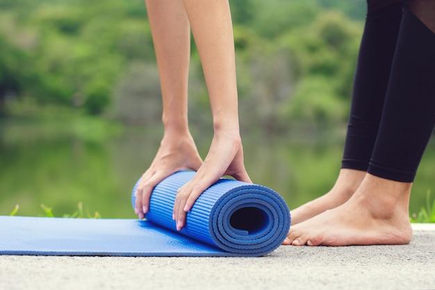 Beschnittenes bild der jungen asiatischen frau, die yogamatte rollt