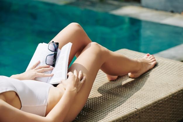 Beschnittenes bild der jungen frau im badeanzug, der auf chaiselongue ruht und ein buch liest