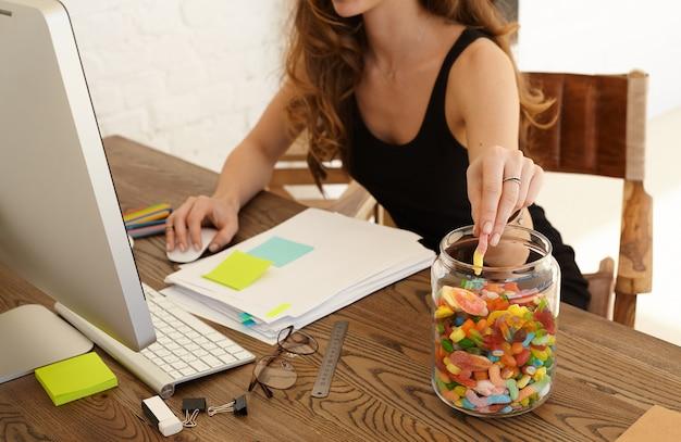 Beschnittenes bild der jungen gestressten frau, die süßigkeiten am arbeitsplatz im büro isst. das mädchen nimmt süßigkeiten aus einem großen glas mit lutschern, die auf einem schreibtisch stehen. stress- und junk-food-konzept