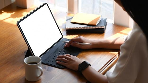 Beschnittenes bild der jungen schönen frau, die auf computertablett mit weißem leerem bildschirm arbeitet.