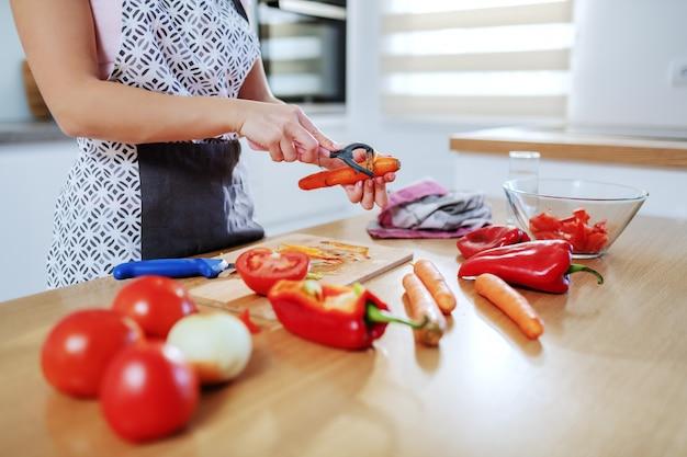 Beschnittenes bild der kaukasischen würdigen frau in der schürze, die karotte schält, während sie in der küche steht. auf der küchentheke stehen tomaten, karotten und paprika.