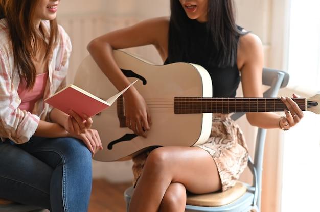 Beschnittenes bild der musiklehrerin, die sitzt und ein buch in der hand hält