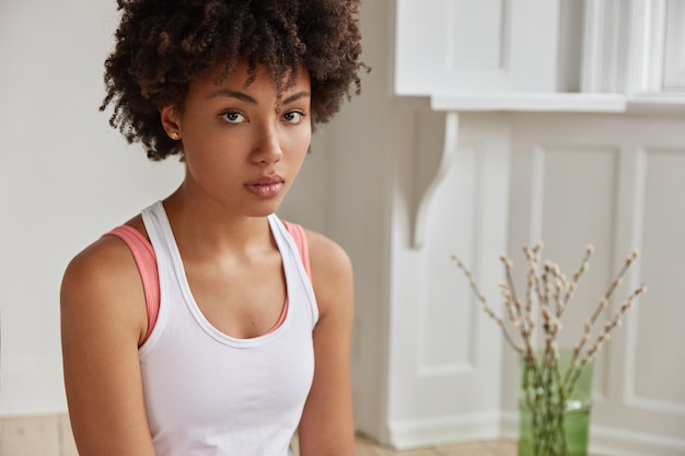 Beschnittenes bild der schönen frau mit dem lockigen haar, der gesunden dunklen haut, gekleidet im lässigen weißen t-shirt, schaut ernsthaft direkt in die kamera.