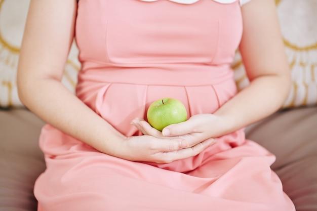 Beschnittenes bild der schwangeren frau, die auf sofa mit grünem apfel in ihren händen sitzt