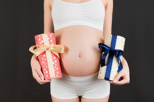Beschnittenes bild der schwangeren frau in der weißen unterwäsche, die zwei geschenkboxen am schwarzen hintergrund hält. ist es ein junge oder ein mädchen? warten auf zwillinge. schwangerschaftsfeier.