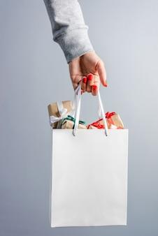 Beschnittenes bild der weiblichen hand mit den roten polierten nägeln, die einfache weiße einkaufstasche halten