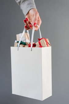 Beschnittenes bild der weiblichen hand mit den roten polierten nägeln, die einfache weiße einkaufstasche voller weihnachtsgeschenkboxen halten