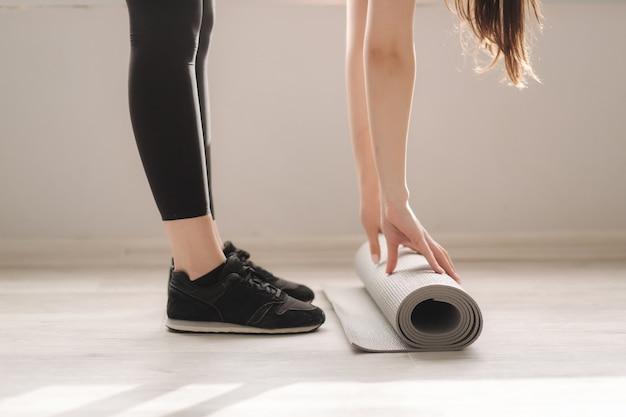 Beschnittenes bild der weiblichen rollenden yogamatte im studio
