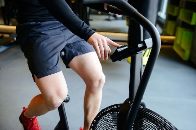 Beschnittenes bild des athletischen mannes unter verwendung des sich drehenden fahrrads