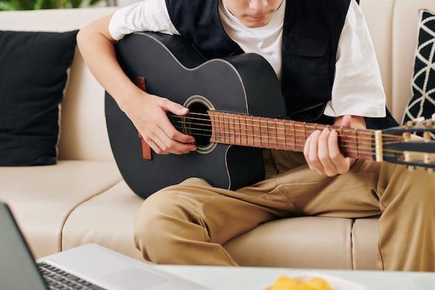 Beschnittenes bild des ernsthaften jugendlichen jungen, der genießt, gitarre vor laptop zu spielen, wenn auf seinem blog gestreamt wird