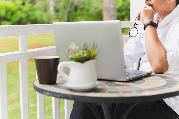 Beschnittenes bild des geschäftsmannes, der seine brille mit laptop auf tisch hält.