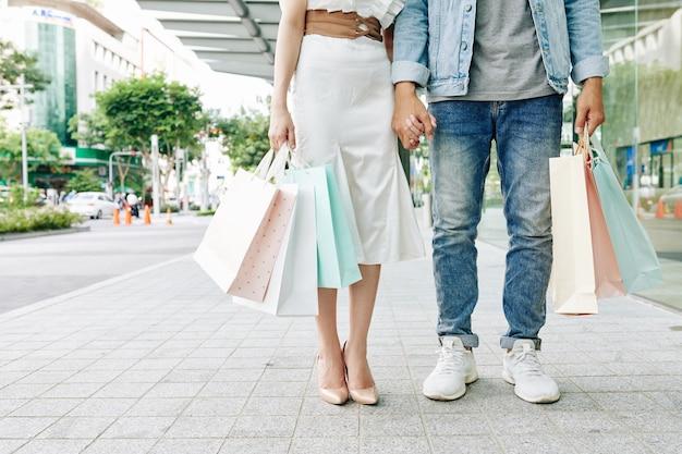 Beschnittenes bild des händchenhaltens des jungen mannes und der jungen frau beim stehen außerhalb der modeboutique mit einkaufstüten