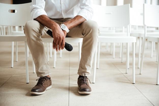 Beschnittenes bild des jungen afrikanischen mannes, der im büro sitzt