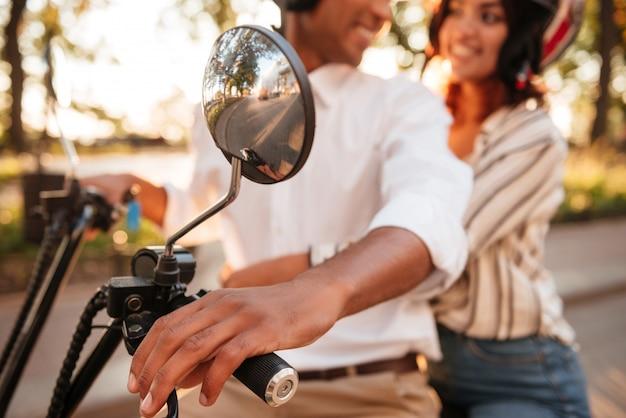 Beschnittenes bild des jungen afrikanischen paares reitet auf modernem motorrad im park und schaut zu einander. bild verwischen