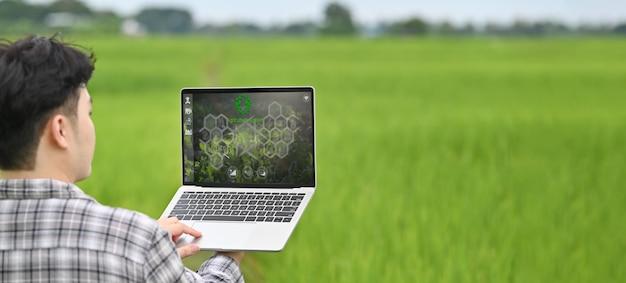 Beschnittenes bild des jungen intelligenten bauern, der einen computer-laptop mit visuellem symbol auf dem bildschirm über reisfeld als hintergrund hält. landwirtschaftstechnologiekonzept.