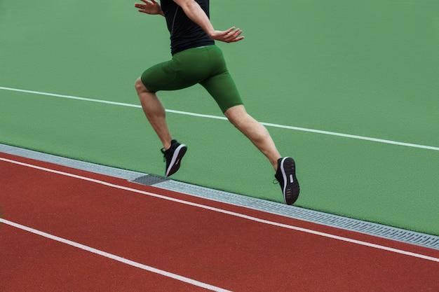Beschnittenes bild des jungen kaukasischen athletenmannlaufs