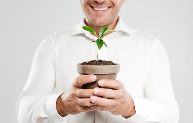 Beschnittenes bild des jungen lächelnden mannes, der pflanze hält.