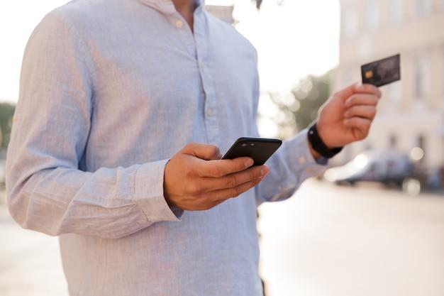 Beschnittenes bild des jungen lässigen mannes unter verwendung des mobiltelefons