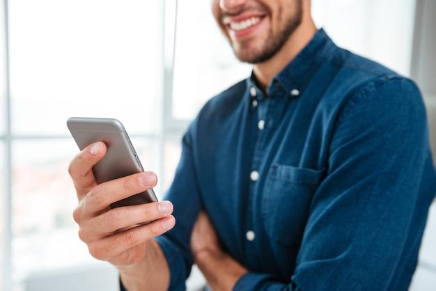 Beschnittenes bild des jungen mannes gekleidet im blauen hemd unter verwendung seines smartphones