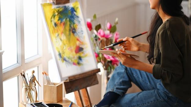Beschnittenes bild des jungen schönen künstlers, der einen pinsel hält und auf leinwand malt