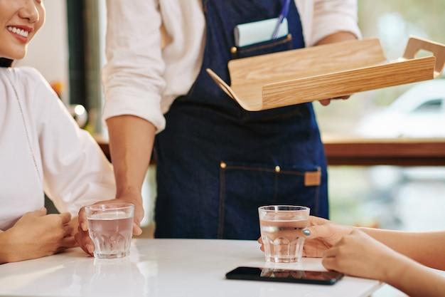 Beschnittenes bild des kellners, der gläser des frischen wassers vor jungen frauen am kaffeetisch setzt