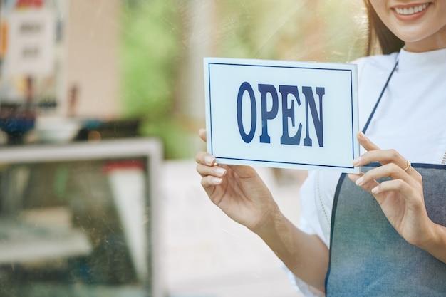 Beschnittenes bild des lächelnden cafébesitzers, der offenes zeichen an glastür des cafés hängt