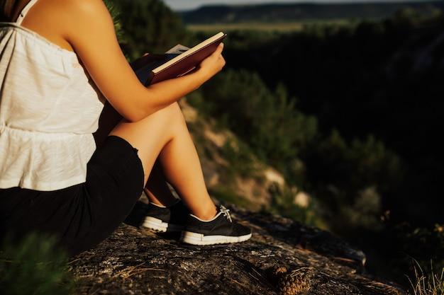 Beschnittenes bild des mädchens auf dem felsen, das buch liest. sie liest buch im sonnigen sommertag.