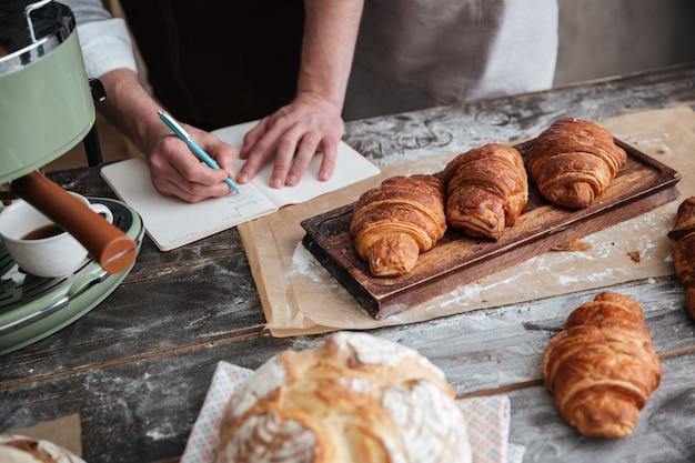 Beschnittenes bild des mannbäckers, der notizen schreibt