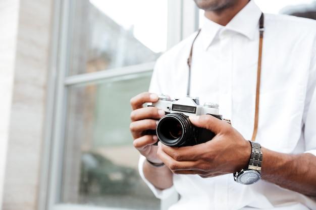 Beschnittenes bild des modemannes auf der straße mit kamera